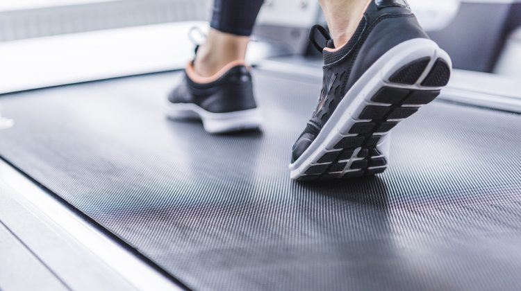 cropped shot of woman in jogging sneakers running on treadmill